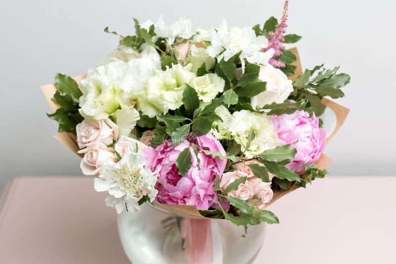 Bouquet léger mignon avec les pivoines roses et les fleurs mélangées sur la raboteuse rose photos libres de droits