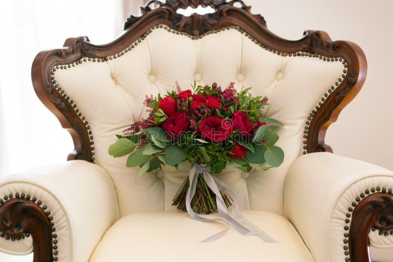 Bouquet l'épousant rouge lumineux des fleurs fraîches et des supports d'eucalyptus sur le fauteuil photos stock
