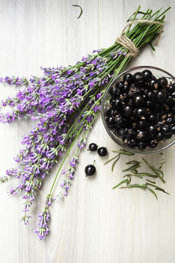 Bouquet of lavender and a cup of fresh black currant on a light wooden background in rustic style royalty free stock photo