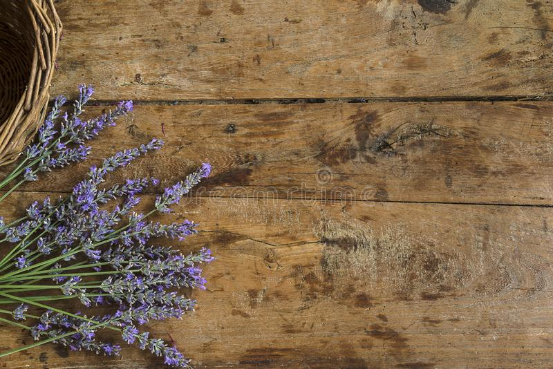 Bouquet of lavender flowers and wicker basket on the vintage wooden background royalty free stock photo