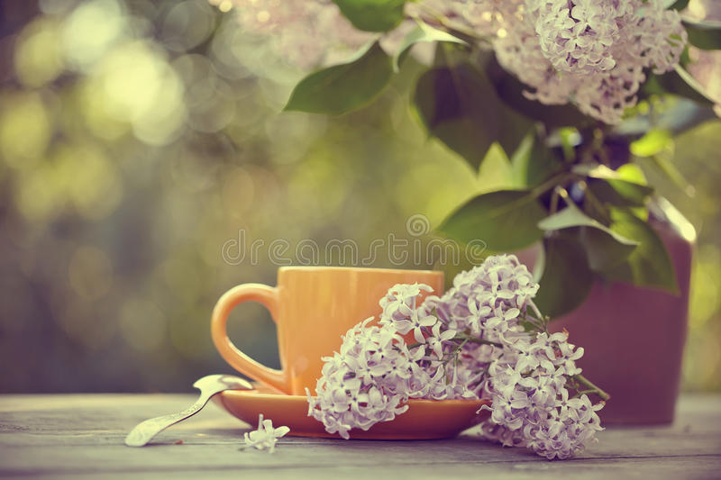 Bouquet of a lilac and cup with a spoon on a table. Bouquet of a lilac and orange cup with a spoon on a table stock photos