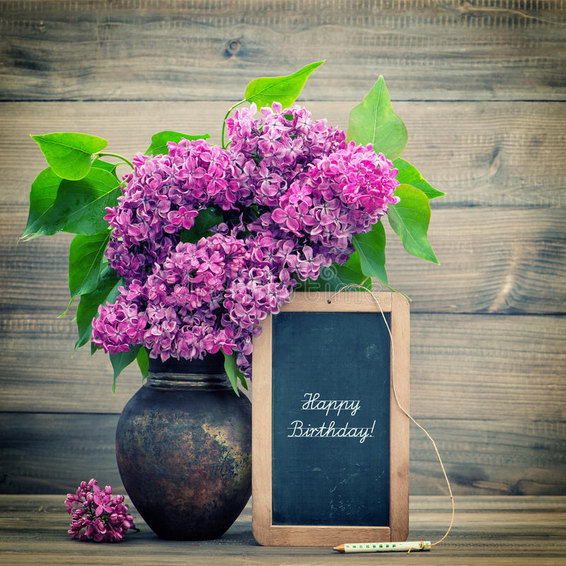 Bouquet of lilac flowers. blackboard with text Happy Birthday!. Bouquet of lilac flowers on wooden background. blackboard with sample text Happy Birthday! retro stock photography