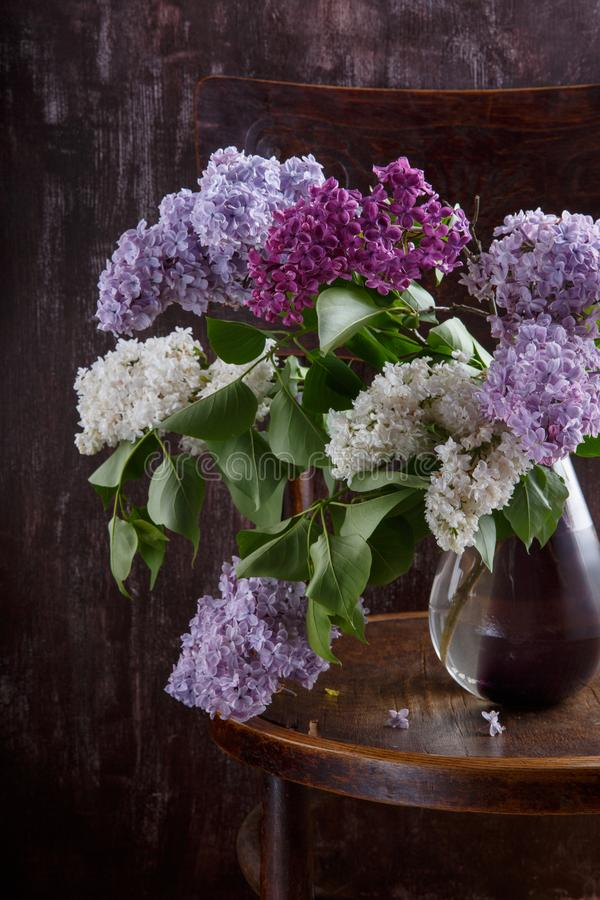 Bouquet of lilac flowers on old vintage chair.  Still life on dark background.  royalty free stock photos