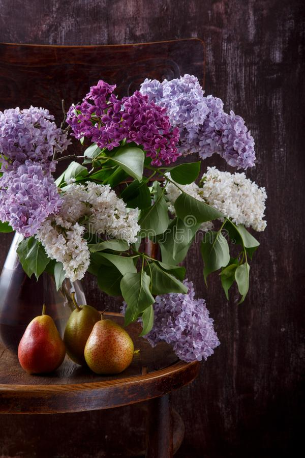 Bouquet of lilac flowers and three pears on old vintage chair.  Still life on dark background royalty free stock images