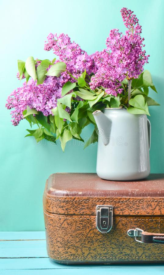 Bouquet of lilac in an old enameled teapot on vintage suitcase on blue background. Retro style still life. Bouquet of lilac in an old enameled teapot on vintage stock image