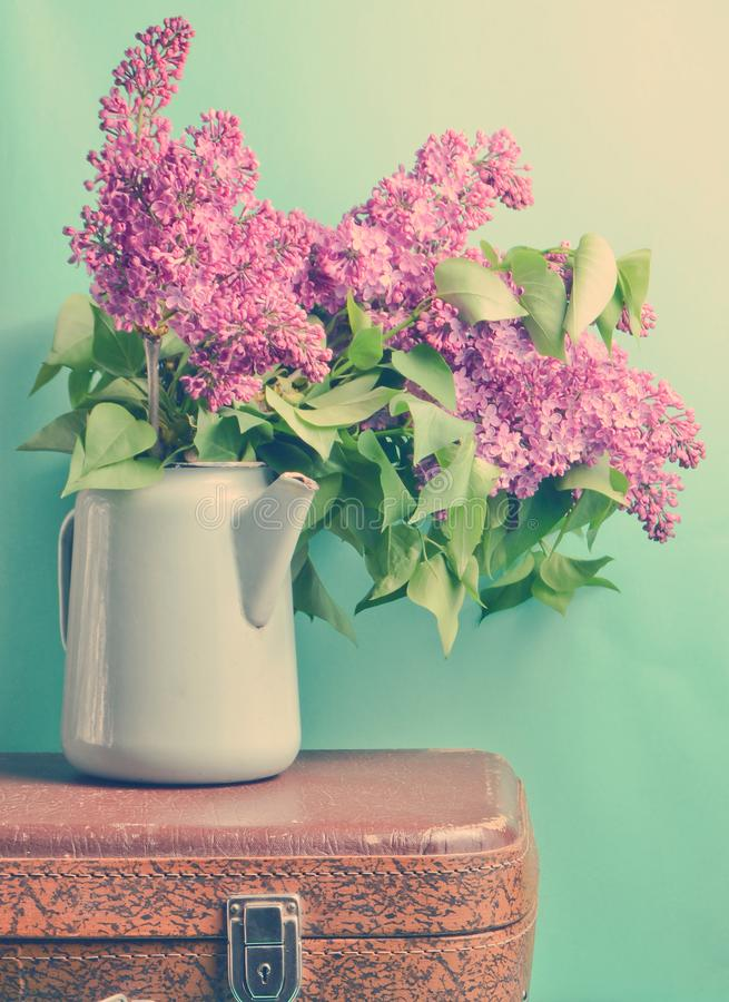 Bouquet of lilac in an old enameled teapot on vintage suitcase on blue background. Retro style still life. Bouquet of lilac in an old enameled teapot on vintage royalty free stock photos