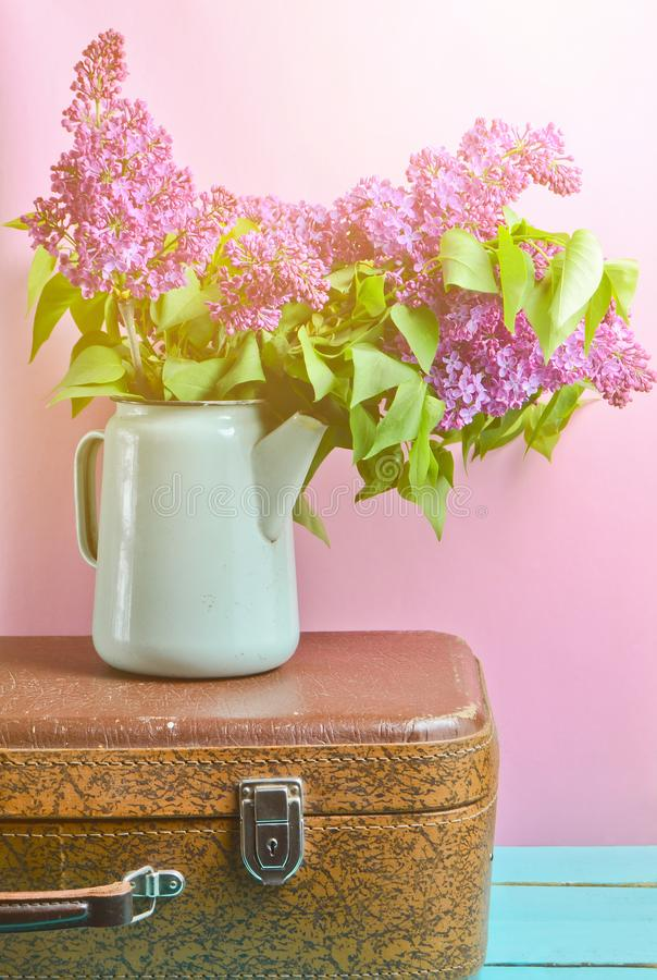 Bouquet of lilac in an old enameled teapot on vintage suitcase on pink background. Retro style still life. Bouquet of lilac in an old enameled teapot on vintage stock photos