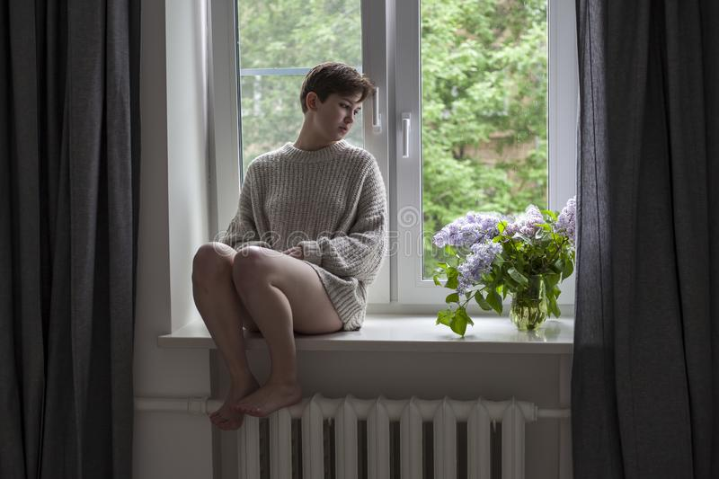 The bouquet of lilac twigs in a transparent jar on white chair as a decoration of interior. The girl sits on the window stock image