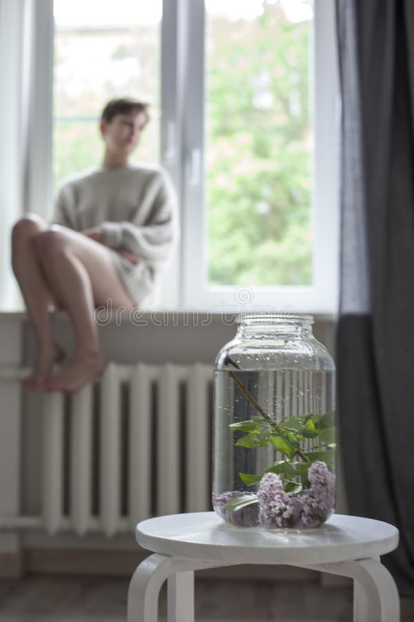 The bouquet of lilac twigs in a transparent jar on white chair as a decoration of interior. The girl sits on the window royalty free stock photography