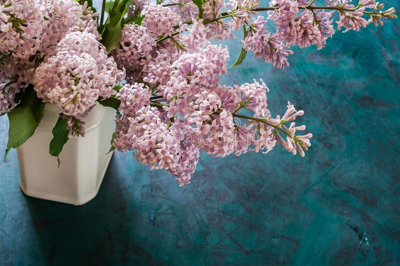 Bouquet of lilac in white ceramic vase on emerald background. Top side view. royalty free stock images