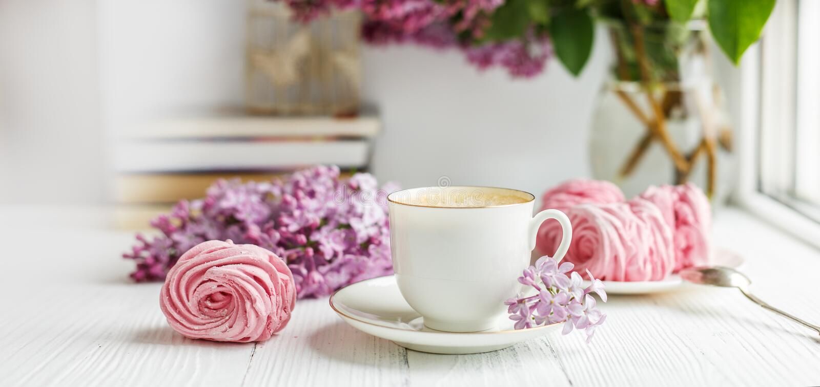 Bouquet of lilacs, cup of coffee, homemade marshmallow and books. Romantic spring morning. Horizontal banner royalty free stock image