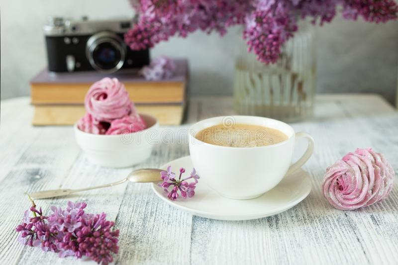 Bouquet of lilacs, cup of coffee, homemade marshmallow and stack of books Retro camera Romantic spring morning stock photos