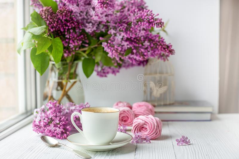 Bouquet of lilacs, cup of coffee, homemade marshmallow and stack of books. Romantic spring morning royalty free stock photos