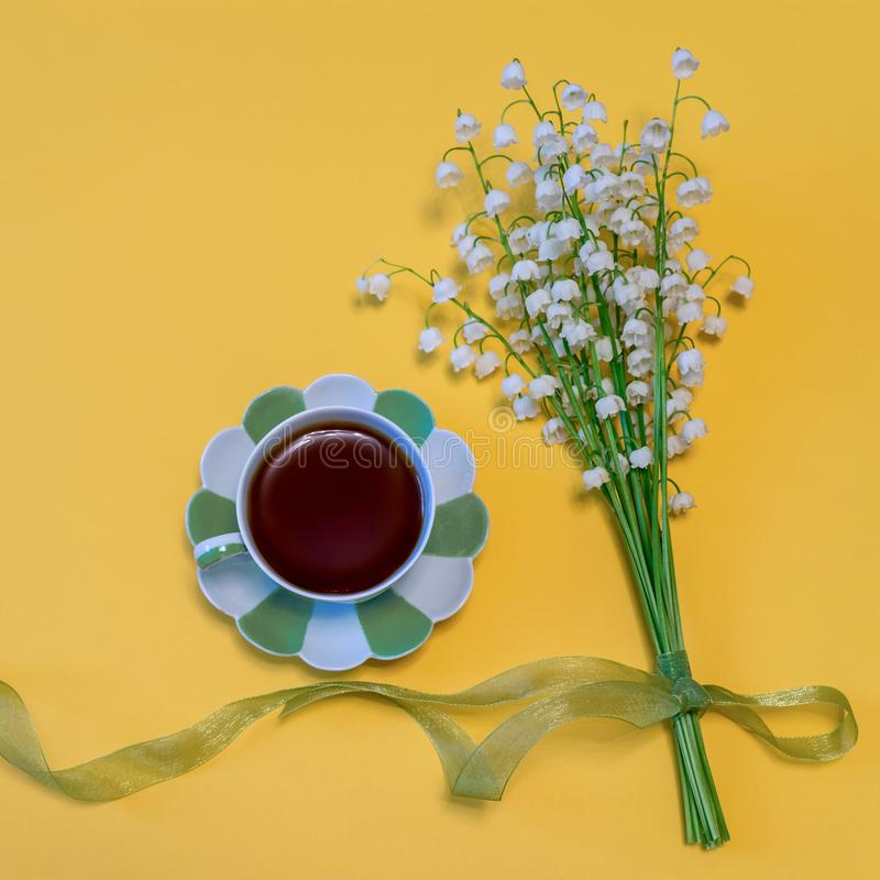 Bouquet of lilies of the valley flowers with green ribbon and tea cup on bright yellow background. Good morning concept. Beautiful. Spring composition in stock photography