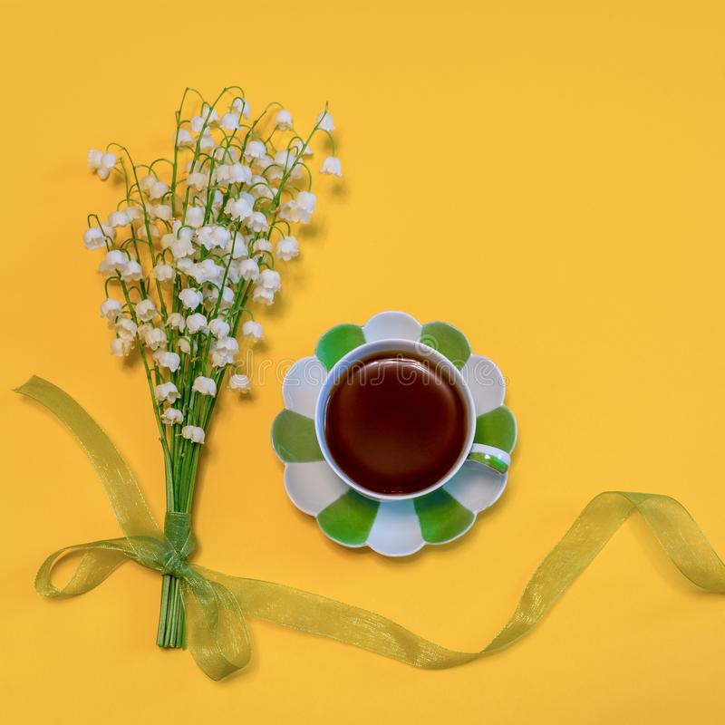 Bouquet of lilies of the valley flowers with green ribbon and tea cup on bright yellow background. Good morning concept. Beautiful. Spring composition in stock image