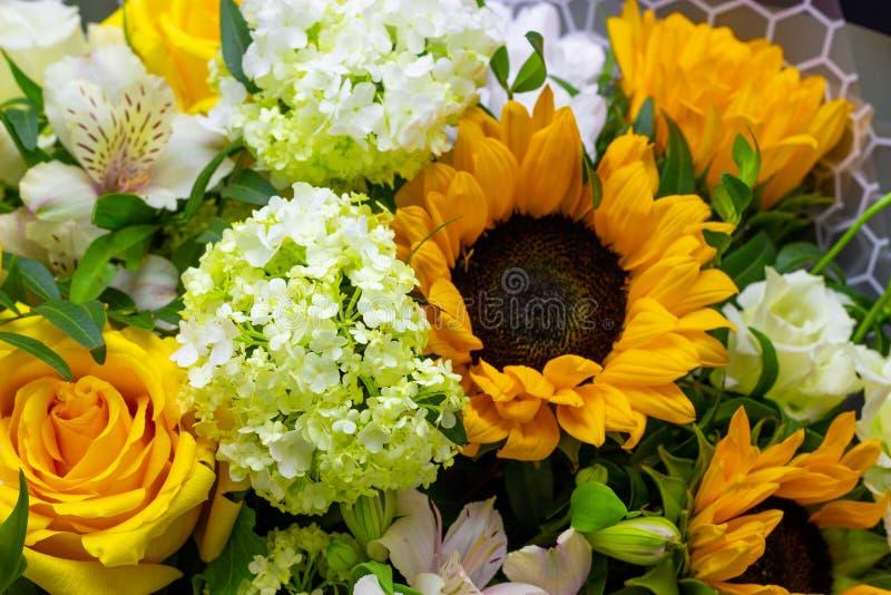 Bouquet lumineux avec les tournesols et la rose jaune, l'eustoma rose et le fond floral de viburnum vert photo stock
