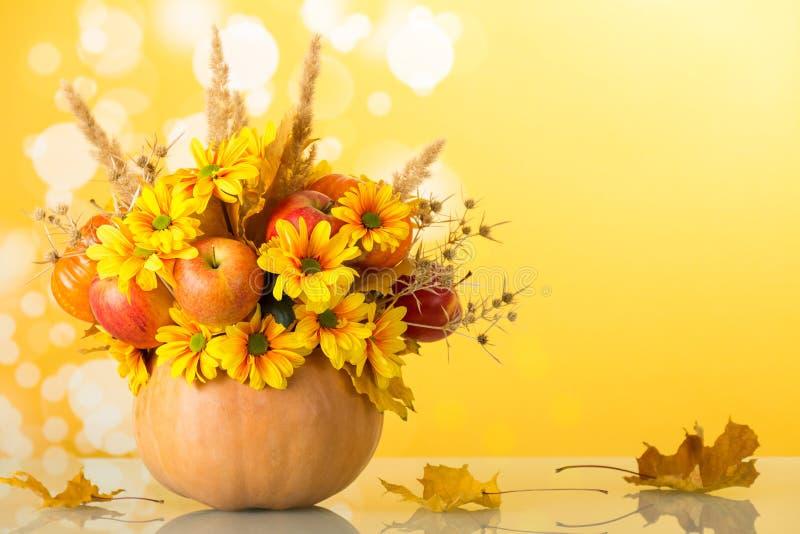 Bouquet lumineux d'automne dans un potiron sur le jaune photo libre de droits