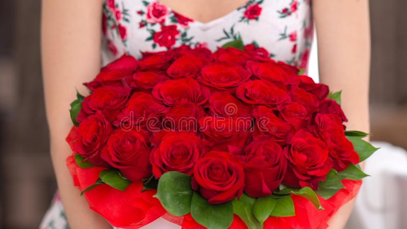 Bouquet of red roses in a white box in the hands of a woman royalty free stock images