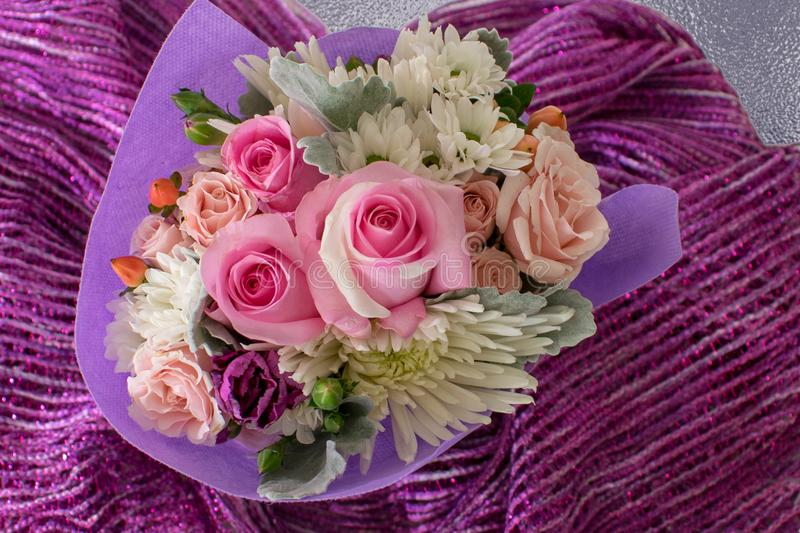 Bouquet of small roses and other mixed flowers on purple fabric. royalty free stock photos