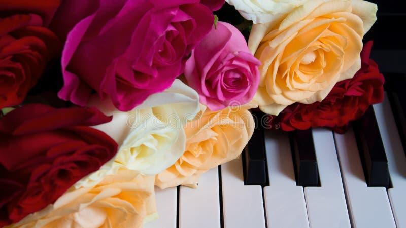 Bouquet mit farbenfrohen Rosen auf den Klaviertasten Rot, Rosa, Beige, Nude, Elfenbein Feiern, Glückwünsche, Musik, Theater stockfotos