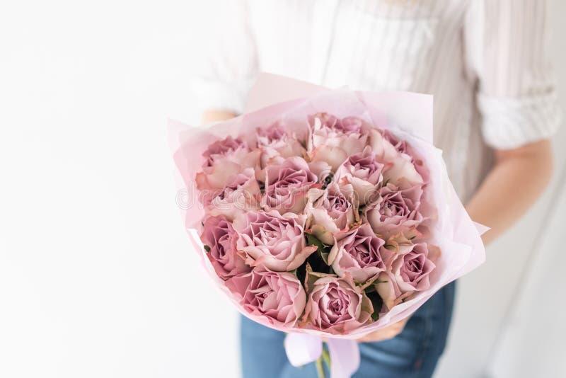 Bouquet mono des roses Bouquet sensible des fleurs m?lang?es chez les mains de la femme le travail du fleuriste ? un fleuriste image libre de droits