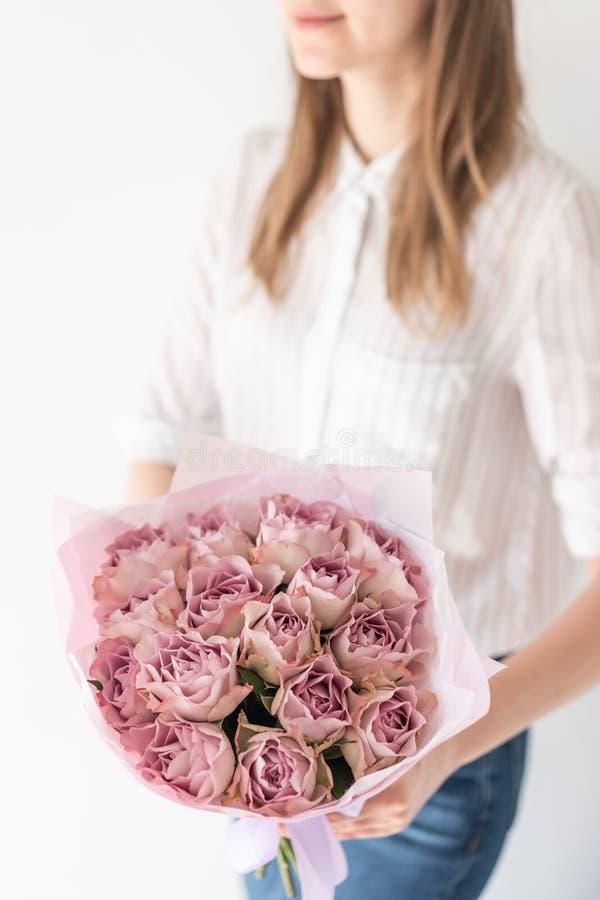 Bouquet mono des roses Bouquet sensible des fleurs m?lang?es chez les mains de la femme le travail du fleuriste ? un fleuriste photographie stock