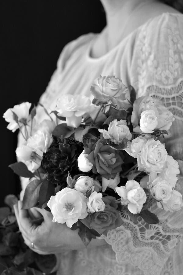 bouquet noir et blanc de fleur dans des mains du ` un s de femme