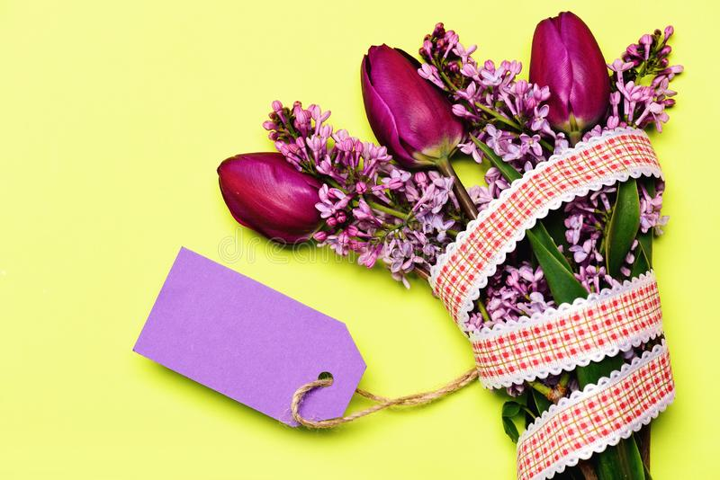 Bouquet with note card: tulip and lilac with purple tag. Bouquet with note card: tulip and lilac flowers with empty light purple tag on lemon yellow background stock image