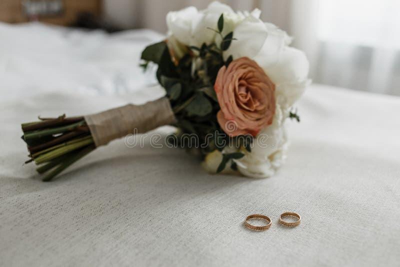 Bouquet nuptiale avec les roses beiges et crémeuses et les anneaux nuptiales sur le lit blanc photo stock
