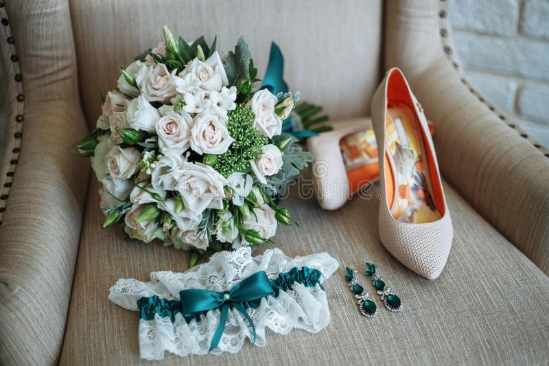 Bouquet nuptiale, boucles d'oreille avec les pierres vertes, jarretière de la jeune mariée, chaussures sur la chaise photographie stock libre de droits