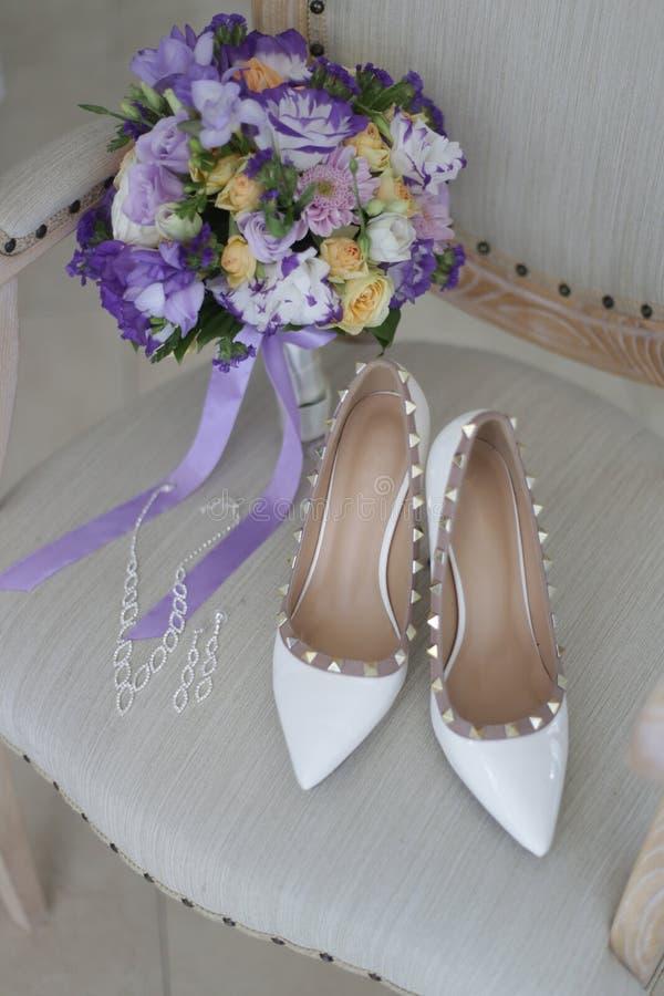 Bouquet nuptiale, boucles d'oreille, colliers, chaussures sur une chaise image stock