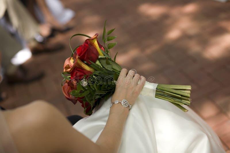 Bouquet nuptiale dans les genoux de la mariée photographie stock libre de droits