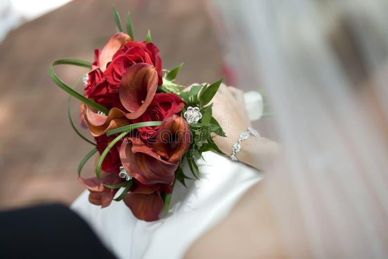 Bouquet nuptiale dans les genoux de la mariée photographie stock