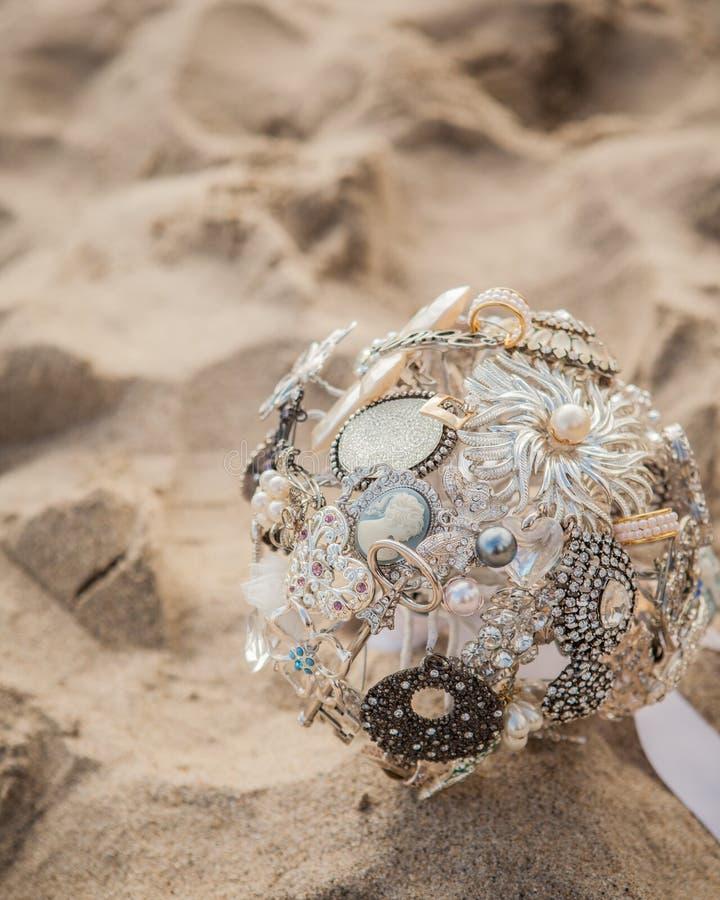 Bouquet nuptiale de broche s'étendant dans le sable image libre de droits