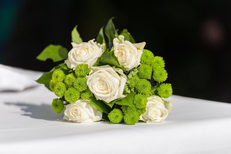 Bouquet nuptiale de fleur sur la table blanche sur le fond noir photo libre de droits