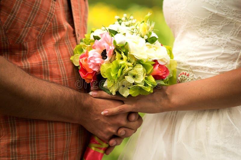 Bouquet nuptiale de jeune mariée tenant le foyer mou image libre de droits