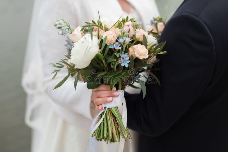 Bouquet nuziale nella mano della sposa immagine stock