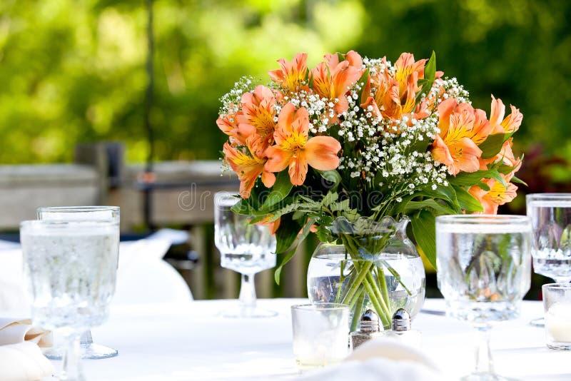 Bouquet orange des fleurs sur une table dans des pots clairs de l'eau pendant une célébration l'épousant photo stock