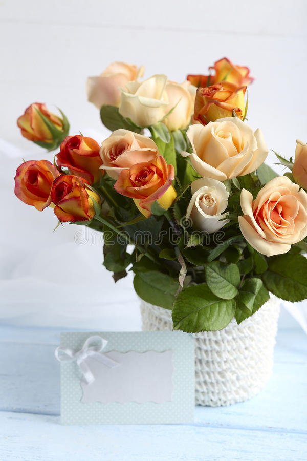 Bouquet of orange roses. In basket on blue wooden background stock image
