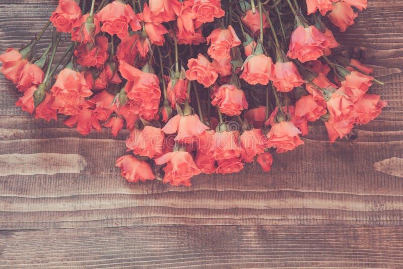 Bouquet of orange roses on wooden board. Spring pattern. Vintage matte stock images