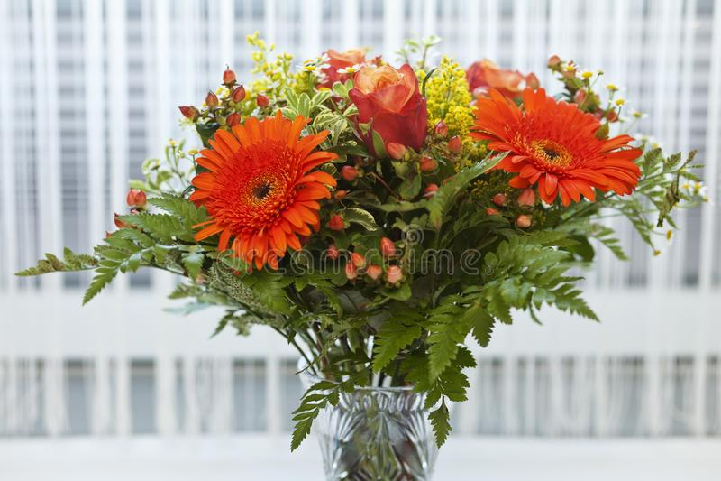Bouquet of orange, yellow and red flowers in a vase. royalty free stock photo