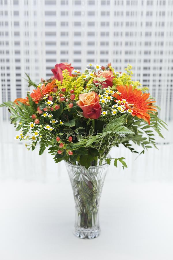 Bouquet of orange, yellow and red flowers in a vase. royalty free stock photography