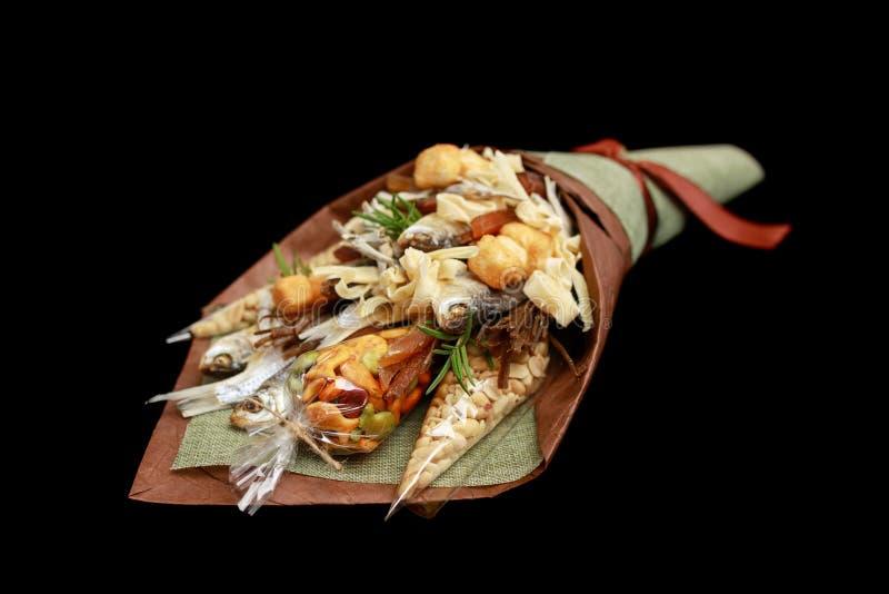 Bouquet original se composant des poissons salés secs, des arachides salées, des biscuits, du pain sec et autres des casse-croûte images libres de droits