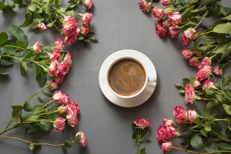 Bouquet of pink bush roses and cup of coffee on shabby chic gray background, top view point. Copy space stock photos