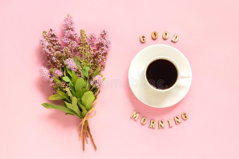 Bouquet of pink flowers, cup of coffee and text Good morning on pink background Greeting card Flat Lay Concept.  royalty free stock images