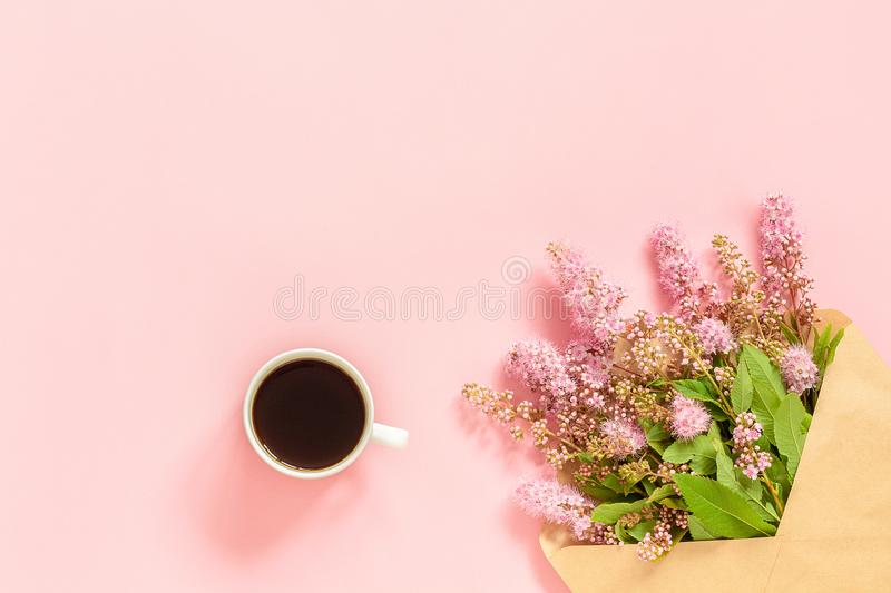 Bouquet of pink flowers in envelope, cup of coffee and a white blank card for text on pink background Concept Good morning or. Bouquet of pink flowers in stock images