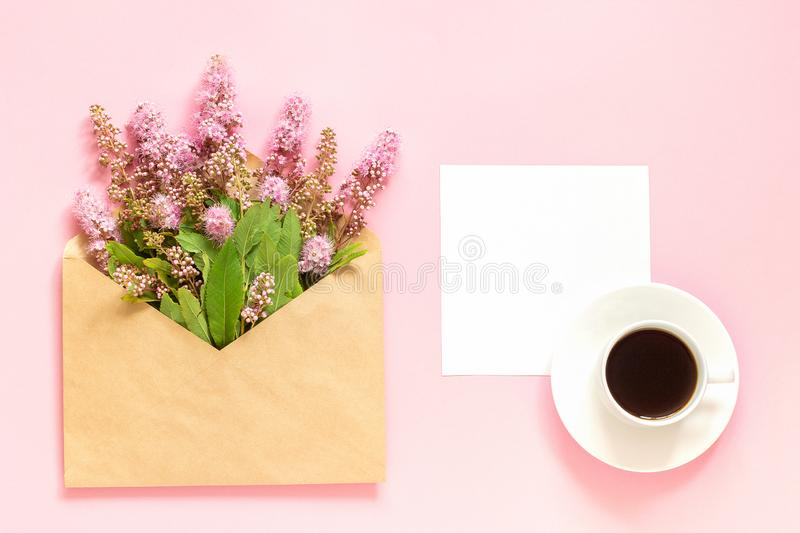 Bouquet of pink flowers in envelope, cup of coffee and a white blank card for text on pink background Concept Good morning or. Bouquet of pink flowers in royalty free stock photography