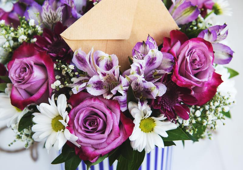 Bouquet of pink flowers. Roses and daisies and envelope royalty free stock photography
