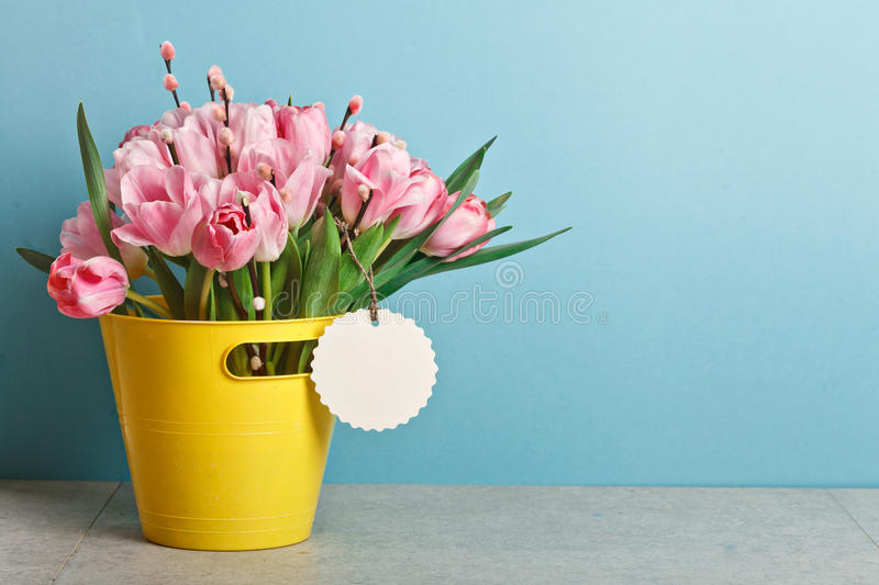 Bouquet of pink fresh tulips with pussy-willow in yellow bucket stock photos