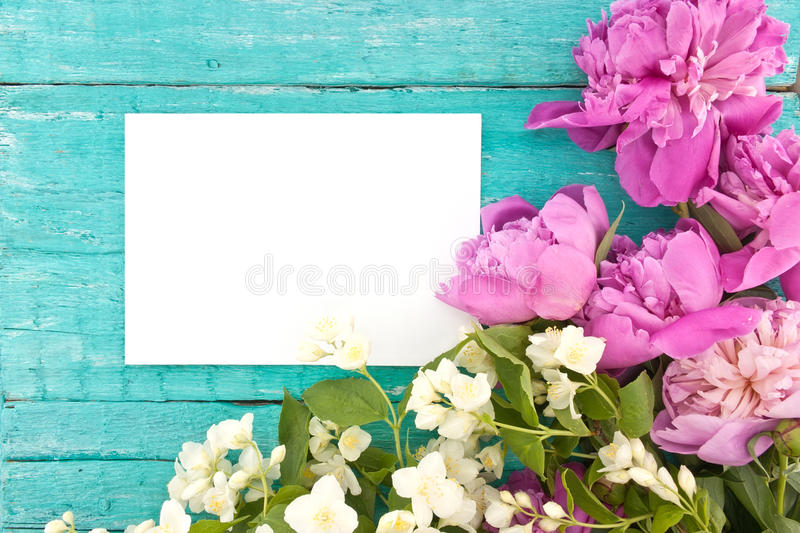 Bouquet of pink peony and mock-orange flowers on turquoise rustic wooden background with empty card for greeting message. stock image